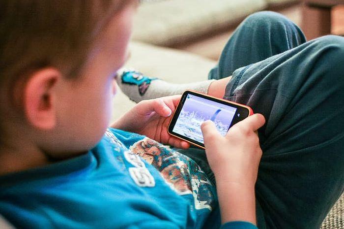 Anak laki-laki main games di ponsel